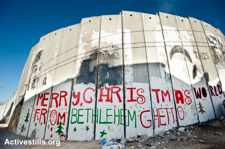 """Graffiti on the Israeli separation wall in the West Bank town of Bethlehem reads, """"Merry Christmas from Bethlehem Ghetto,"""" December 16, 2010."""