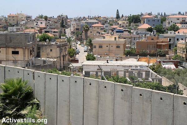 Illustrative photo: The separation wall runs Baqa Al-Gharbiya, July 16, 2015. (Activestills.org)