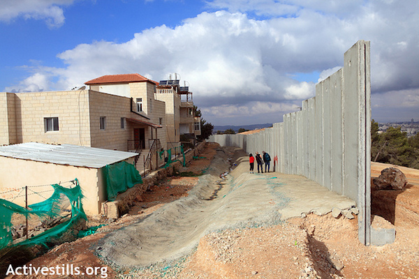 Illustrative photo of Israel's separation wall abutting Palestinian homes. (Anne Paq/Activestills.org)