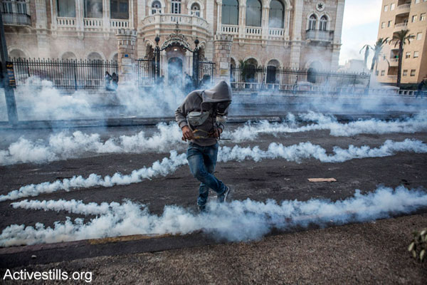 A Palestinian youth kicks a tear gas canister during clashes with the Israeli army in the West Bank city of Bethlehem, November 20, 2015. (photo: Activestills.org)