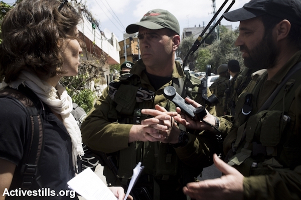 Israeli army officers speak to Breaking the Silence director Yuli Novak as the army prevented a Breaking the Silence tour from proceeding through the occupied city of Hebron, April 4, 2014. (Keren Manor/Activestills.org)