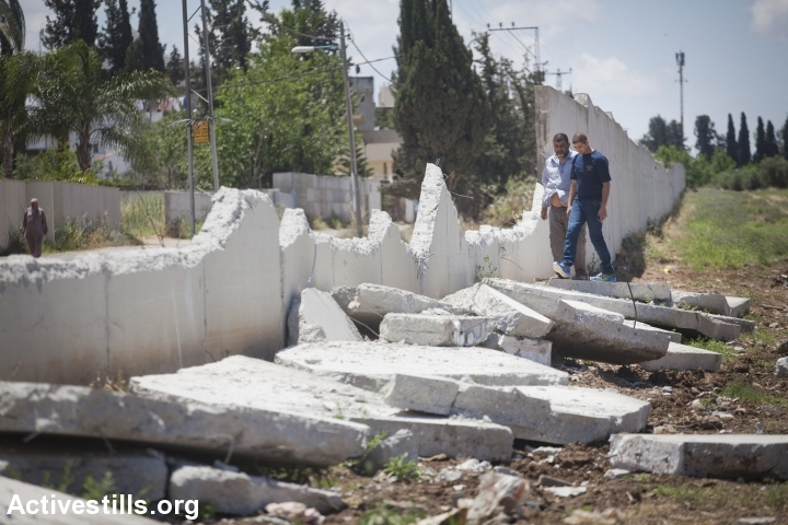 A damaged section of the wall separating Lod's Palestinian neighborhood of Pardes Shanir and the Jewish town of Nir Tzvi, 2013. (Oren Ziv/Activestills.org)