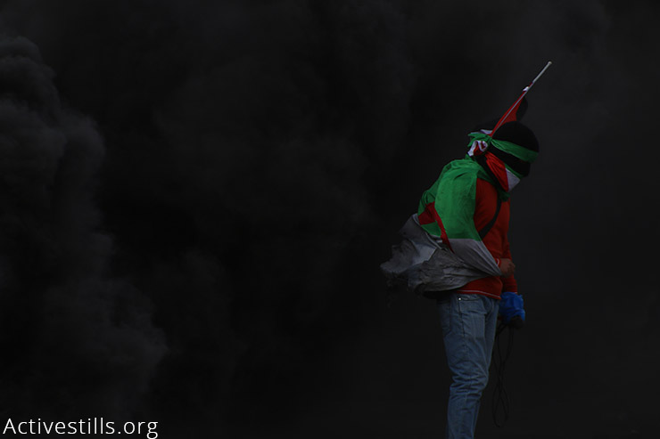 A Palestinian youth is engulfed in smoke from burning tires during clashes between Palestinian university students and Israeli security forces outside the compound of the Israeli army's Ofer Military prison, near the West Bank town of Betunia, November 3, 2015. (Activestills.org)