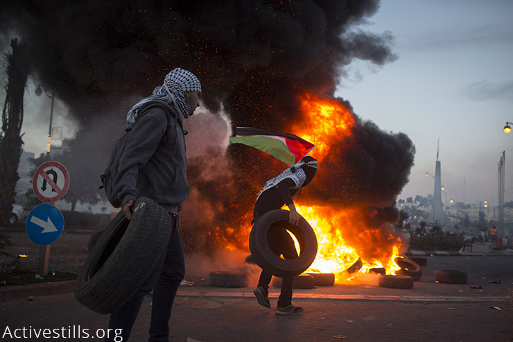 Palestinian youth burn tires during clashes with Israeli forces near the illegal Israeli settlement of Beit El, just north of Ramallah, West Bank, November 20, 2015.Over 10 protesters were hit with live ammunition by Israeli forces. (Activestills.org)