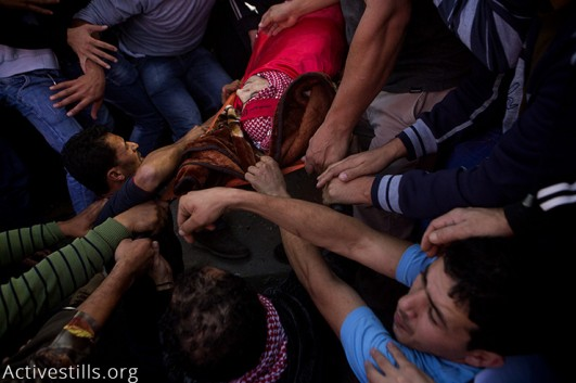Friends and relatives carry 19-year-old Khalid al-Jawabreh during his funeral in Al-Arroub camp, West Bank, November 27, 2015. Khalid was killed the day before by Israeli soldiers during clashes. His funeral was attended by hundreds and was followed by clashes. More than 100 Palestinians have been killed by Israeli forces since the beginning of October, while at least 16 Israelis have been killed in the same period. More than 9,000 Palestinians and over 80 Israelis were injured, and 1,195 Palestinians including 177 underage children were arrested in the same period. (Activestills.org)