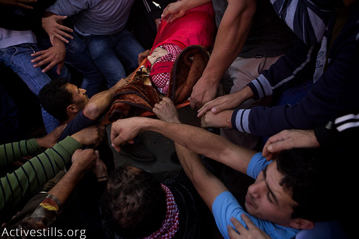 Friends and relatives carry 19-year-old Khalid al-Jawabreh during his funeral in Al-Arroub camp, West Bank, November 27, 2015. Khalid was killed the day before by Israeli soldiers during clashes. His funeral was attended by hundreds and was followed by clashes. (Activestills.org)