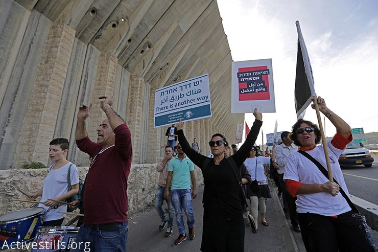 Israeli and Palestinian peace activists march along the main West Bank highway, Road 60, during a demonstration near the 'tunnels checkpoint' between the West Bank city of Beit Jala and Jerusalem, on November 27, 2015. Hundreds of protesters gathered to denounce the occupation and all violence in the region. (Activestills.org)