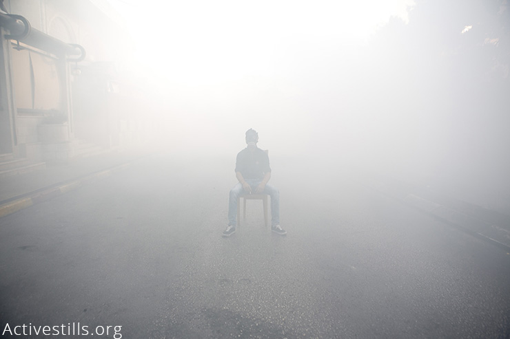 A Palestinian youth sits in a chair in the middle of tear gas during clashes with the Israeli soldiers in Bethlehem, West Bank, November 27, 2015. More than 100 Palestinians have been killed by Israeli forces since the beginning of October, while at least 16 Israelis have been killed in the same period. More than 9,000 Palestinians and over 80 Israelis were injured, and 1,195 Palestinians including 177 underage children were arrested in the same period. (Activestills.org)