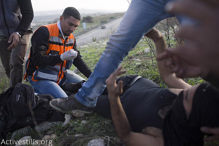 Medics treat a Palestinian youth who was struck by live ammunition, shot by the Israeli army during clashes outside the Ofer military prison, near the West Bank town of Betunia, November 27, 2015. (Activestills.org)