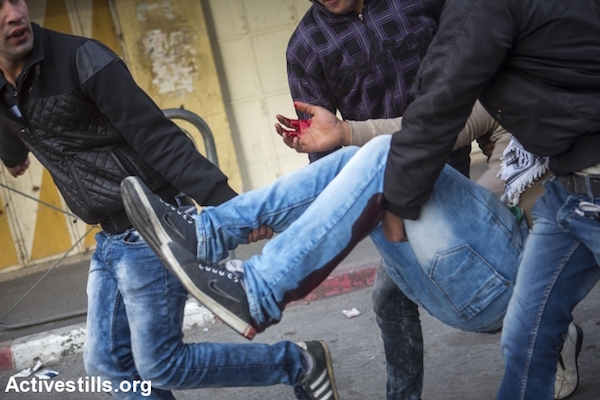 Palestinians carry an injured youth who was shot by an Israeli sniper during clashes with the Israeli army in the occupied West Bank city of Hebron, November 4, 2015. (Anne Paq/Activestills.org)