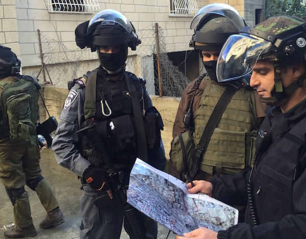 Israeli security forces inspect a map during a home demolition in Shuafat refugee camp, East Jerusalem, December 2, 2015. (Israel Police)