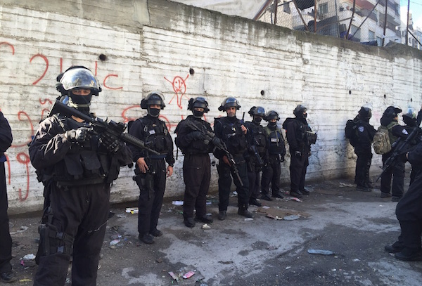 Israeli security forces line up in a street in Shuafat refugee camp during a home demolition, East Jerusalem, December 2, 2015. (Israel Police)