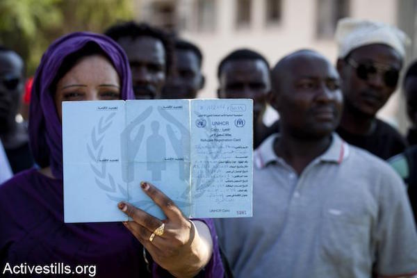 A Sudanese woman protesting outside the Israeli Interior Ministry in Tel Aviv displays a UNHCR card issued in Cairo, October 14, 2012. (Oren Ziv/Activestills.org)