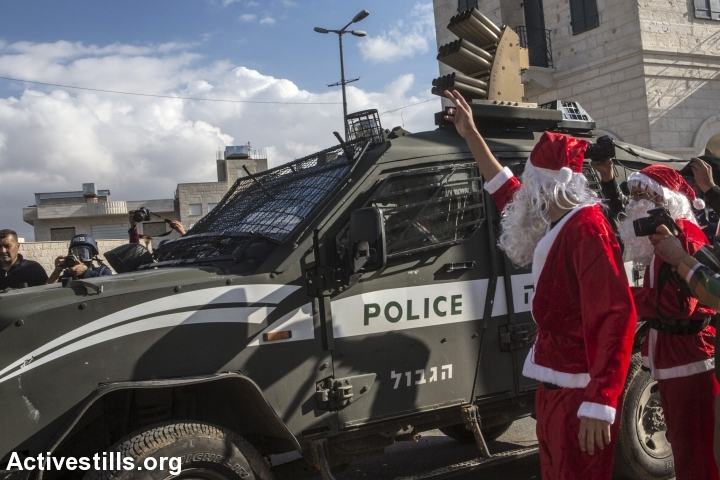 Palestinians dressed up as Santa Claus demonstrate at the separation wall, Bethlehem, December 18, 2015. (photo: Anne Paq/Activestills.org)