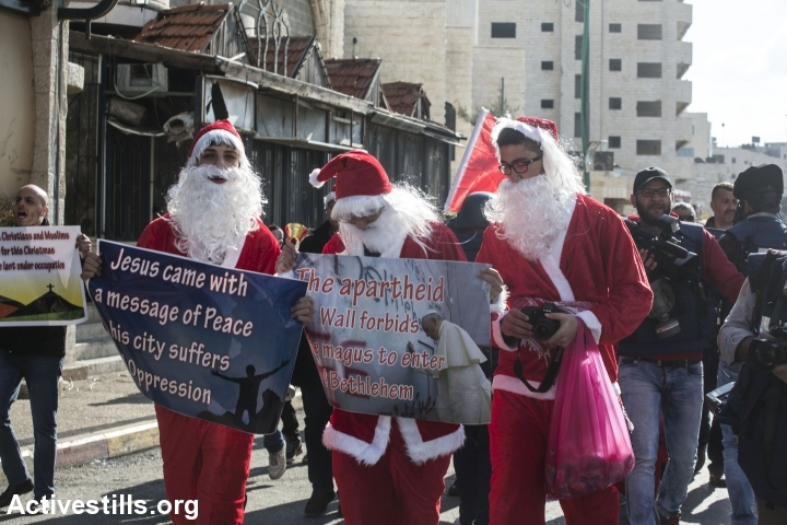 Palestinian protesters dressed up as Santa Claus march during clashes between Palestinian youths and the Israeli army in the West Bank city of Bethlehem, December 18, 2015. (photo: Anne Paq/Activestills.org)