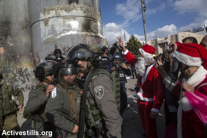 Palestinians dressed up as Santa Claus confront Israeli soldiers during a protest against the occupation in the West Bank city of Bethlehem, December 18, 2015. (photo: Anne Paq/Activestills.org)