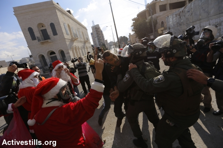 Palestinians disguised as santa Claus shout slogans next to Israeli border policemen during a protest against the occupation in the West Bank city of Bethlehem, December 18, 2015. (photo: Mustafa Bader/Activestills.org)
