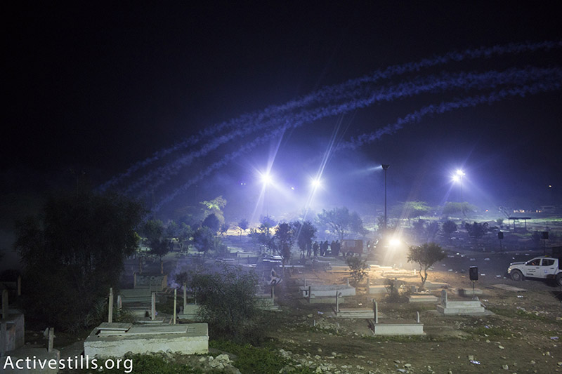 Clouds of tear gas cover the Rahat cemetary, after Israeli police dispersed the funeral of Sami al-Jaar, January 18, 2015. Sami Ziadna, 42, suffocated to death from tear gas inhalation during the clashes, which wounded 22 others. The Southern District police commander admitted that the police had come to an agreement with the city leadership that no officers would enter the cemetery during the funeral. (photo: Activestills.org) | Click here for more background on the incident.