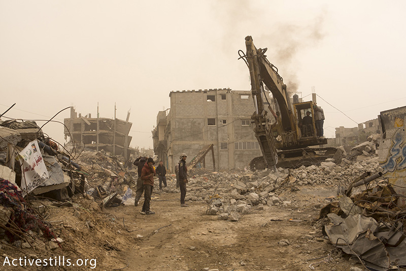 A bulldozer clears rubble in one of the destroyed quarters of the Shuja'iyya neighborhood in Gaza City, February 11, 2015. Six months after a ceasefire put an end to 'Operation Protective Edge,' 100, 000 Palestinians remained displaced, with many live in extremely dire conditions. Building materials are scarce, since the Gaza Strip is under Israeli blockade. (photo: Activestills.org) | Click here for more on the situation in Gaza following last summer's war.