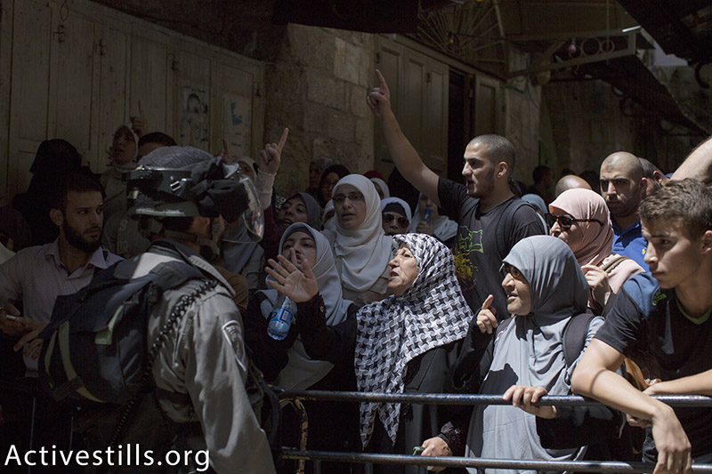 Israeli Border Police prevent Palestinians from entering the Aqsa Mosque compound in Jerusalem's Old City following clashes inside, July 26, 2015. Clashes erupted this year after increasing numbers of Jewish Israelis and prominent right-wing politicians began ascending to the Temple Mount, considered the holiest place in Judaism, threatening to subvert the delicate status quo established with the Muslim authorities, in place since 1967. (photo: Activestills.org) | For more on the roots of the clashes surrounding Al-Aqsa, click here.
