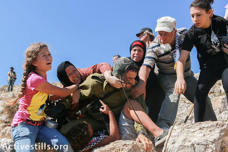 Members of the Tamimi family prevent from an Israeli solider from arresting Mohammed Tamimi, 11, during the weekly protest against the occupation in the West Bank village of Nabi Saleh, August 28, 2015. Photos of the arrest went viral in Israel, while the media completely ignored the Tamimi family's version of the events. (photo: Activestills.org) | For more on the photos that introduced the world to Nabi Saleh, click here.