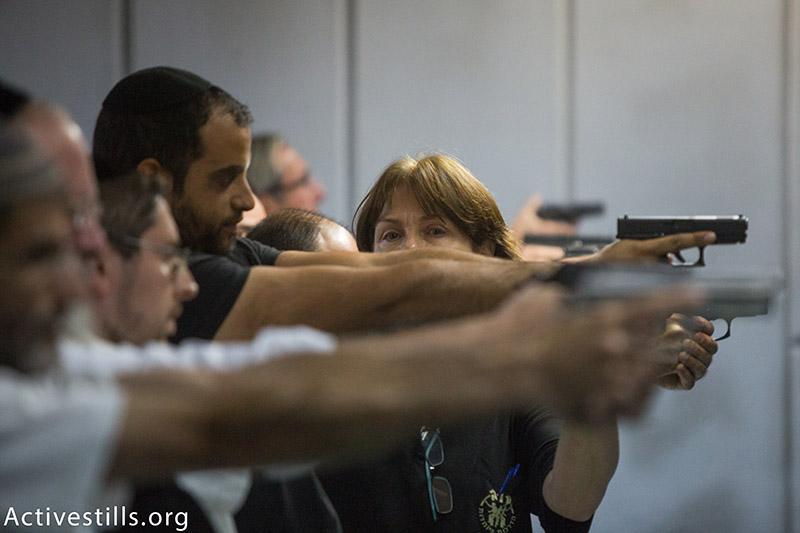 Israelis take part in target practice inside a Jerusalem gun shop, October 15, 2015. Gun shop owners reported a dramatic rise in demand for weapons and other self defense weapons as violence continued to swell around Jerusalem. (photo: Activestills.org) | Do more guns make Israelis any safer? Click here for more.