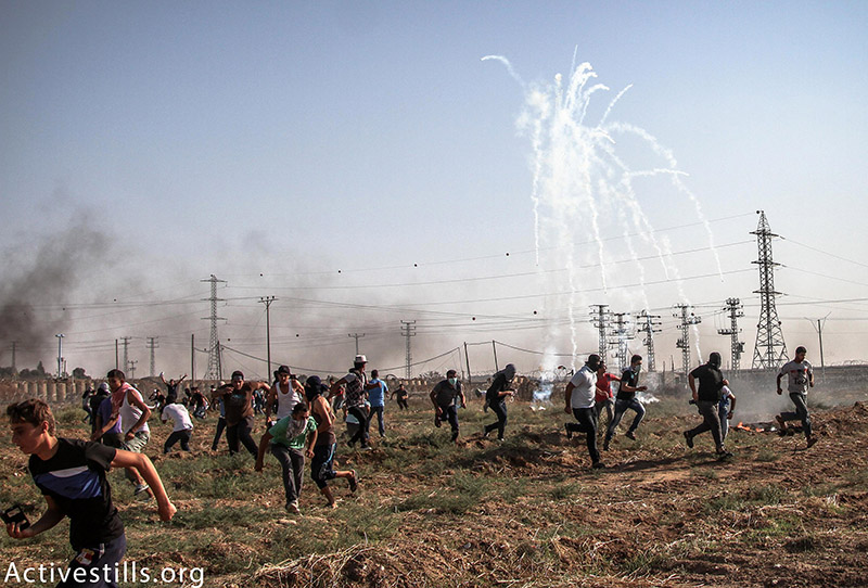 Palestinians run from tear gas during a protest near the Nahal Oz crossing, northern Gaza Strip, October 16, 2015. Thousands of Palestinians marched towards the border from different areas in the Strip following calls for a 'day of rage.' Two Palestinians were killed by Israeli forces during the demonstrations. Over 140 Palestinians, 20 Israelis, one American and one asylum seeker have been killed since October 1. (photo: Activestills.org) | Click here for more on Israel's control of the Gaza Strip.