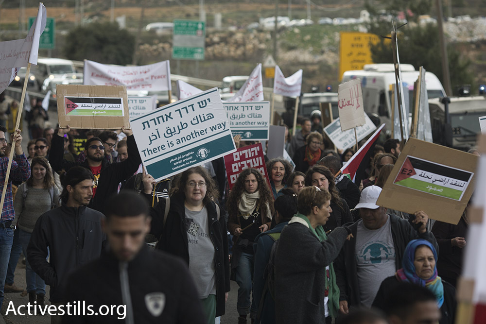 Jewish Israelis and Palestinians march along the major Hebron-Jerusalem highway in the southern West Bank demanding an end to the occupation, Beit Jala, West Bank, January 15, 2016. (Oren Ziv/Activestills.org)