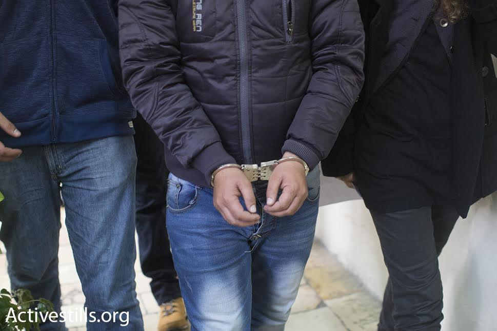 A Palestinian human rights activist is led to the Jerusalem District Court in handcuffs following his arrest Tuesday morning, January 20, 2016. (photo: Oren Ziv/Activestills.org)