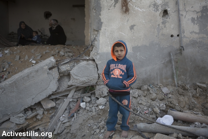 A Palestinian child stands in front of his destroyed home in the Tuffah neighboorhood of Gaza city, Gaza Strip, February 9, 2015. Six months after the Israeli military offensive, tens of thousands of Palestinians are still displaced. (photo: Anne Paq/Activestills.org)