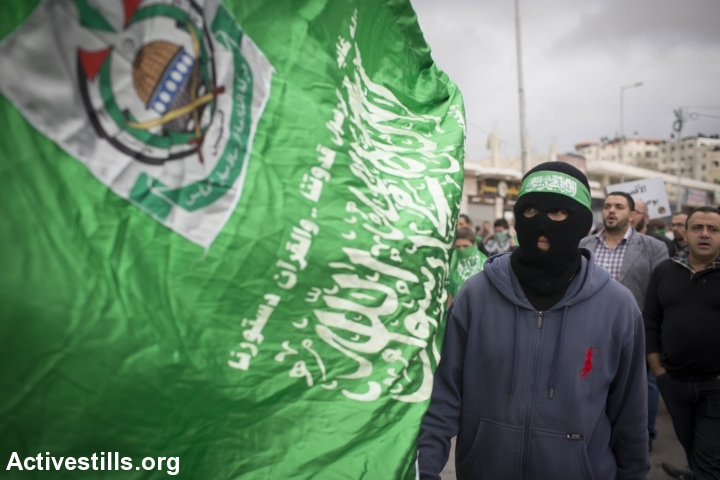A Palestinian holds a Hamas flag during a rally of supporters of the Hamas movement against the restrictions on the Al-Aqsa mosque compound, at the Qalandia checkpoint between Ramallah and Jerusalem City, on October 31, 2014.