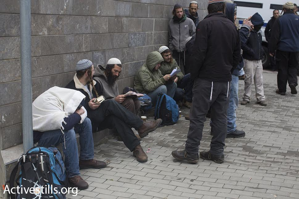 Supporters of Amiram Ben-Uliel, who is suspected of carrying out the Duma murders, pray outside the courthouse in Lod, Israel, January 3, 2015. (photo: Oren Ziv/Activestills.org)