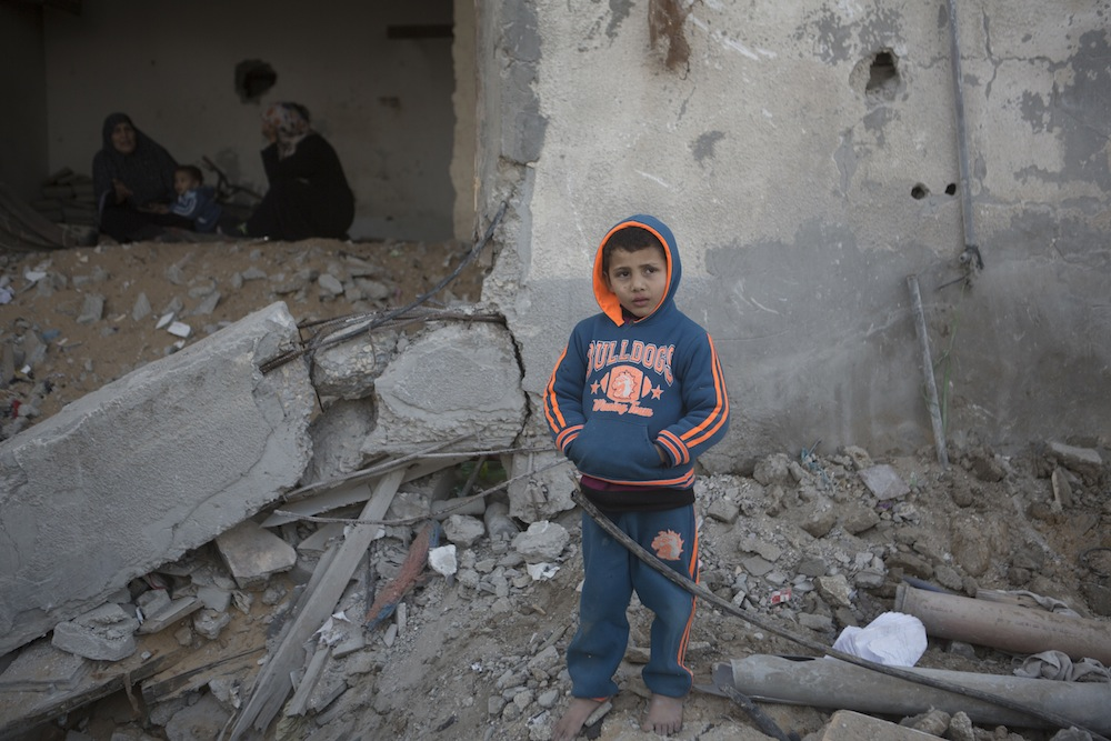 A Palestinian child stands in front of his destroyed home in the Tuffah neighboorhood of Gaza city, Gaza Strip, February 9, 2015. (photo: Anne Paq/Activestills.org)