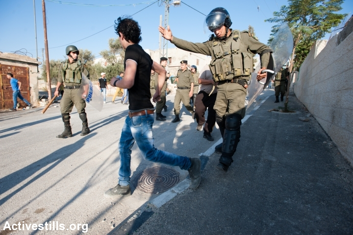 Palestinian Authority police attempt to prevent youth in Aida Refugee Camp from clashing with Israeli forces, Bethlehem, West Bank, September 27, 2013. (Ryan Rodrick Beiler/Activestills.org)