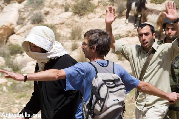 A Jewish member of Ta'ayush uses his body to protect Palestinian shepherds from Israeli settlers in the south Hebron Hills, 2008. (Keren Manor/Activestills.org)