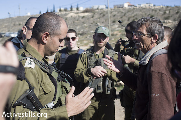 A member of Ta'ayush speaks to Israeli army officers during a direct action in solidarity with Palestinian residents of the South Hebron Hills, January 17, 2016. (Oren Ziv/Activestills.org)