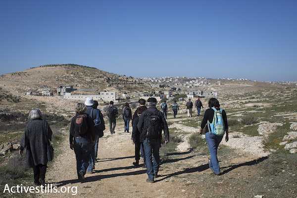 A group of Ta'ayush activists walk toward a Palestinian hamlet in the South Hebron Hills on a recent Saturday, January 17, 2016. The activists' presence is often enough to prevent settlers from targeting Palestinians and to deter the army from kicking them off their land. (Photo by Oren Ziv/Activestills.org)
