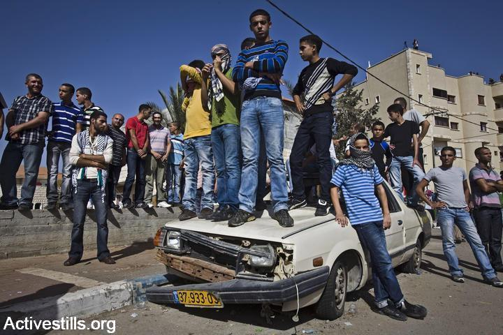 Palestinian citizens of Israel stand on a car during clashes in Umm al Fahem, Israel, October 27, 2010. (photo: Oren Ziv/Activestills.org)