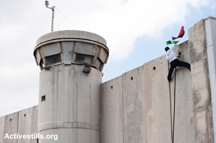 A Palestinian scales the Israeli separation wall and plants his flag during a protest at Bethlehem checkpoint, March 30, 2012. (Activestills.org)