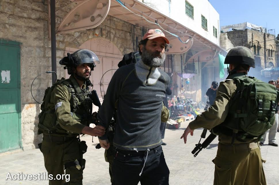 Israeli soldiers arrest activist Kobi Snitz during a protest in Hebron marking 22 years since the Ibrahimi Mosque Massacre, February 20, 2016. (photo: Oren Ziv/Activestills.org)