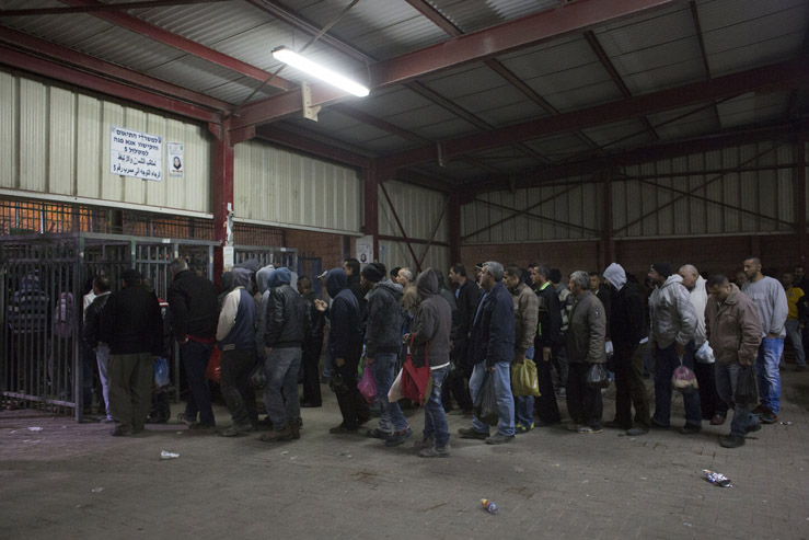 Palestinian laborers with work permits issued by the Israeli military, as well as high school students, wait to cross the Qalandiya checkpoint separating the West Bank city of Ramallah and Jerusalem, in the early hours of Febuary 25, 2016. (Activestills.org)