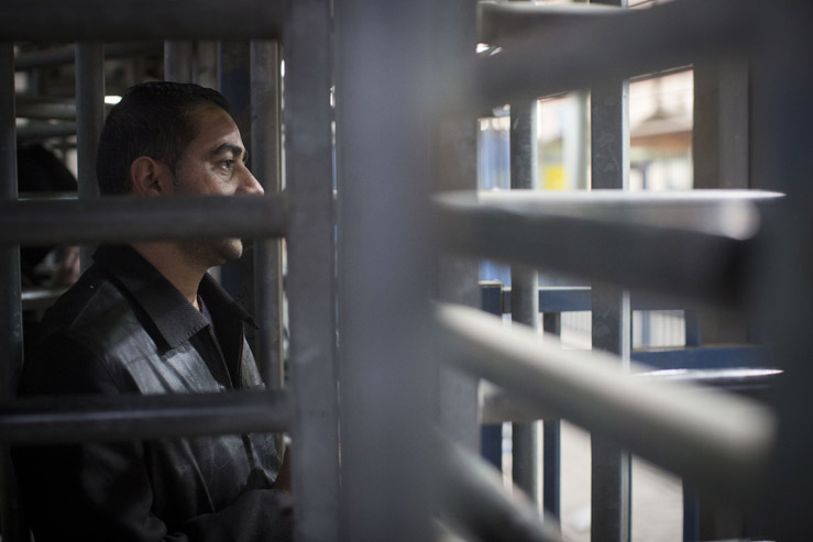 A Palestinian man stands waiting in a locked turnstile in one of the Israeli army's dozens of checkpoints controlling Palestinian movement. In order to pass through, Palestinians must have a permit from the Civil Administration. The regulations concerning how to obtain such a permit were not published in Arabic. (Activestills.org)