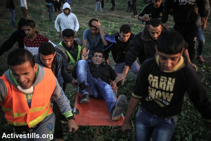 Palestinians carry a protester who was shot during clashes with Israeli forces near the Israel-Gaza border, near Nahal Oz crossing, Nobember 20, 2015. (Ezz Zanoun/Activestills.org)