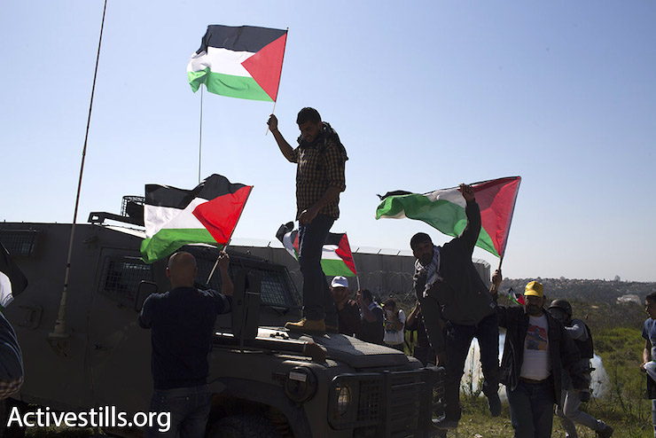 Palestinian protesters try and place Palestinian flags on an Israeli army jeep near Bil'in. The army declared the protest illegal and used stun grenades and tear gas to disperse it, February 16, 2016. (Oren Ziv/Activestills.org)