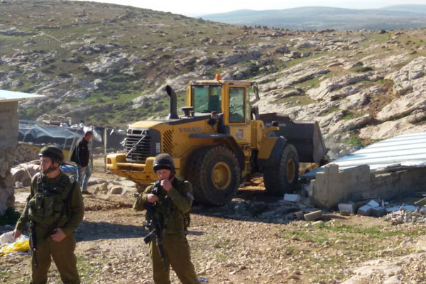 Israeli soldiers guard a bulldozer demolishing Palestinian structures in Khirbet Jenbah, which is part of what the army calls 'Firing Zone 918,' February 2, 2016. (Nasser Nawaj'ah/B'Tselem)
