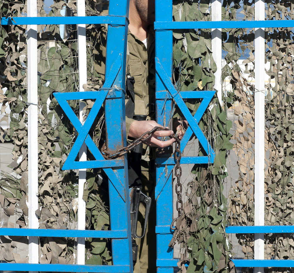 An Israeli soldier locks a fence at the border with Lebanon. (Shutterstock.com/Maxmacs)