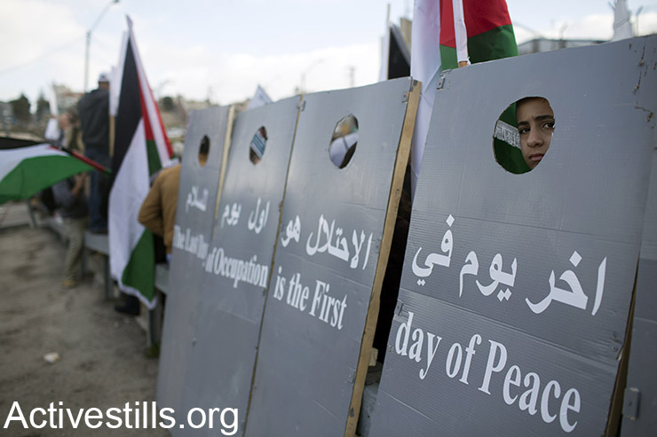 Activists hold mock sections of the Separation Wall during a protest against the occupation on the West Banks main Jerusalem-Hebron highway in full view of Israeli settlers, Beit Jala, West Bank, January 15, 2016. (Activestills.org)