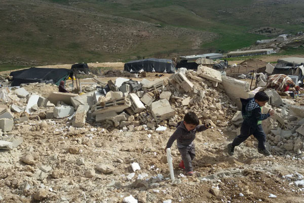 Palestinian children play in the rubble left after the Israeli military demolished 24 Palestinian structures in Khirbet Jenbah, which is part of what the army calls 'Firing Zone 918,' February 2, 2016. (Nasser Nawaj'ah/B'Tselem)
