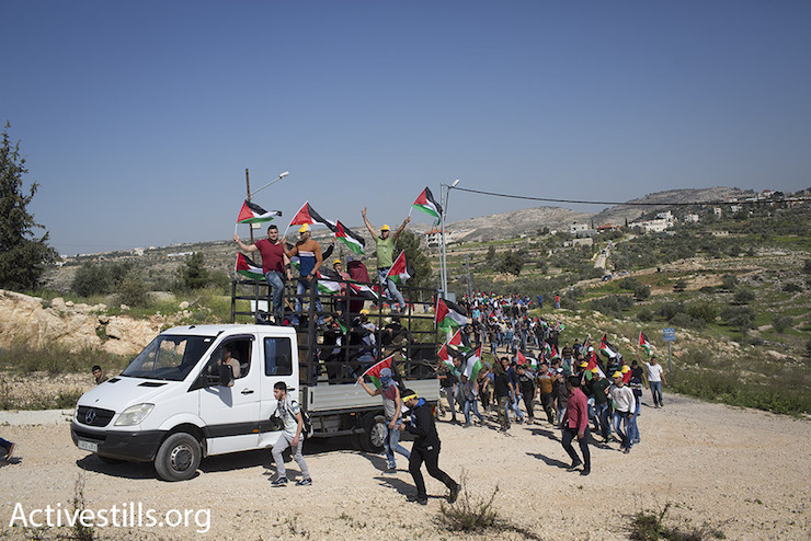 Palestinians, Israelis and foreigners march toward the separation wall that cuts the village of Bil'in off from its land, February 19, 2016. (Oren Ziv/Activestills.org)