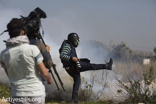 A press photographer kicks away a tear gas canister that Israeli troops fired toward a group of journalists, Bil'in, February 19, 2016. (Oren Ziv/Activestills.org)
